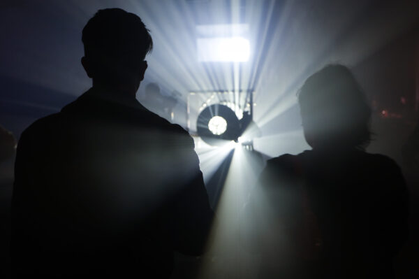 Two people are silhouetted between a bright white light. Image is for the blog post titled CALL OUT: Equality,Diversity & Inclusion Consultant