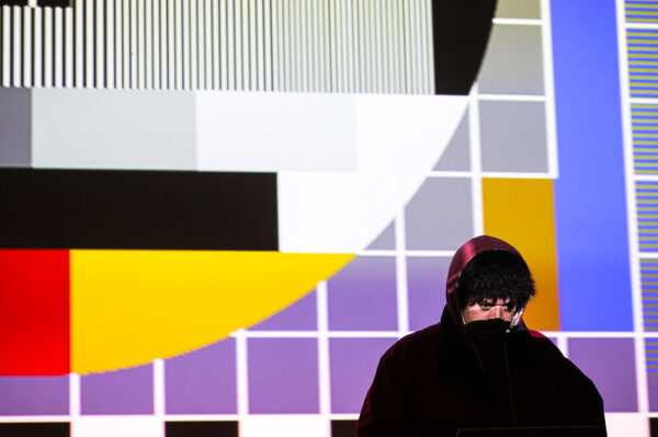 Man in shadow with colourful screen behind him