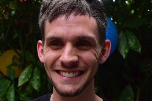 Man smiling against bush