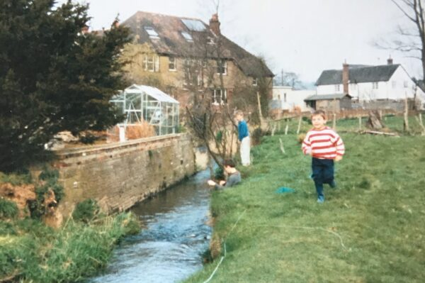A photograph of a photograph of Michael as a child, in a white and red jumper running beside a stream in a field with two boys behind him and some houses in the distance.